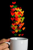 Hand holding white cup with bokeh heart shapes — Stock Photo