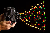 Old movie camera taking photo of bokeh hands holding — Stock Photo