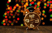 Bokeh spots of lights with alarm clock on wood — Stockfoto