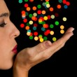 Woman blow round bokeh spots off her hand — Stock Photo