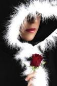 Portrait of sad woman in black cape and rose artistic conversion — Stock Photo