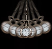 Pocket watch swinging on a chain black background — Stock Photo
