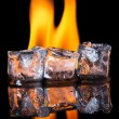Ice cubes with flame on shiny black surface — Stock Photo