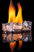 Cubes de glace avec la flamme sur une surface noire brillante — Photo