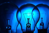 Row of light bulbs n a bright blue background — Stock Photo
