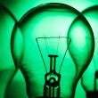 Row of light bulbs on a bright green background — Stock Photo