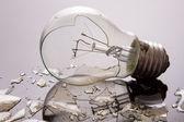 Broken light bulb on shiny surface — Stock Photo