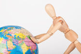 Wood mannequin push a world globe in disrespect isolated — Stock fotografie