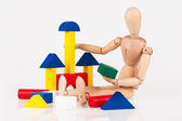 Small wood mannequin sit building colourful blocks isolated on w — 图库照片