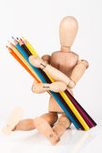 Small wood mannequin sitting with bunch of colour pencil isolate — Stock Photo