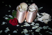 Old used ballet slippers lying on floor with rose and petal — Stock Photo