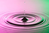 Water drop close up with concentric ripples on colourful pink and green surface — Stock Photo