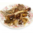 Residues from food, bones from fish and chicken on a plate — Stockfoto
