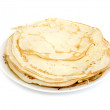 A lot of pancakes on a plate isolated on white background — Stock Photo