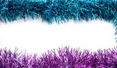 Christmas blue and purple tinsel streamers — Stock Photo