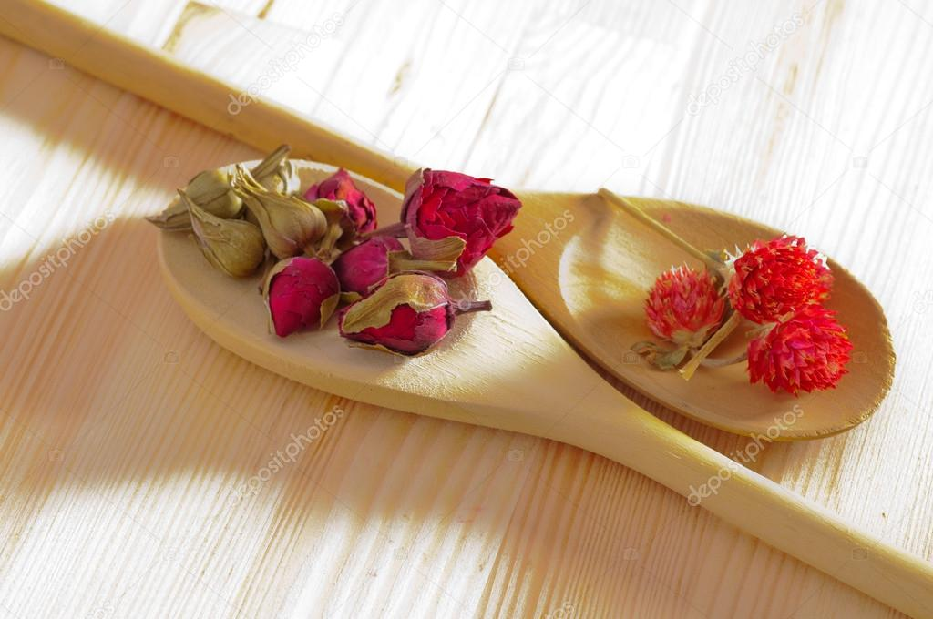 Dry floral herbal tea on wood spoon over wooden table  Stock Photo #17397417
