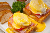 Eggs benedict on bread with tomato and ham — Stock Photo