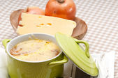 Oinion soup with melted cheese and bread on top — Stock Photo