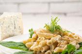 Italian pasta penne gorgonzola and pine nuts — Stock Photo