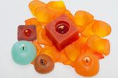 Verschüttete blütenblätter der orange-rose um die aromatherapie kerze — Stockfoto