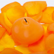 Foto Stock: Spilt petals of orange-rose around aromatic candle