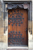 Old wooden door with decorative, forged metal hinges — Stock Photo