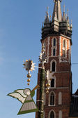 Christmas decorations with playing on trumpet angel on Main Market Square in Krakow during xmas and new year time, at the background Mariacki Church, Cracow, — Stock Photo