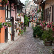 Street with half-timbered medieval houses in Eguisheim village along the famous wine route in Alsace, France — Stock Photo #39858645