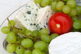 Cheese with white grapes and tomato — Stock Photo