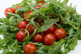 Heap of ruccola leaves and cherry tomatoes — Stock Photo