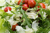 Heap of ruccola, lettuce leaves and cherry tomatoes — Stock Photo