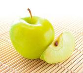 Maçã amarela com fatias de maçã sobre a esteira de bambu — Foto Stock