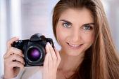 Portret pięknej uśmiechający się młoda kobieta za pomocą dslr aparat fotograficzny — Zdjęcie stockowe