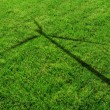 Wind Generator Turbine Shadow on the Grass - Stock Photo