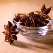Star Anise in the Glass Bowl on Wooden Table - Stock Photo