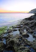Skały w morzu przed piękny zachód słońca — Zdjęcie stockowe