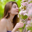 Young Beautiful Woman Smelling a Pink Sakura Flowers — Stock Photo