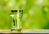 Glass Full of Water against the Green Nature Background — Stock Photo