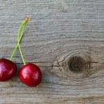 dwa świeże dojrzałe czerwone słodkie wiśnie na drewniane tła — Zdjęcie stockowe