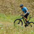 Mountain Biker Riding His Bike Through the Meadow — Stock Photo