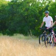 Young Happy Couple Riding Mountain Bikes Outdoor — Stock Photo #31409333