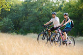 Young Happy Couple Riding Mountain Bikes Outdoor — Stock Photo