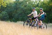 年轻快乐的夫妻骑着山地车户外 — 图库照片