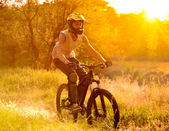 Cyclist Riding the Bike on Trail in the Summer Forest at Sunrise — Foto de Stock