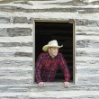 Stock Photo: Cowboy Looking Out Window