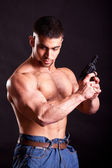 Bodybuilder with gun — Stock Photo