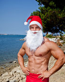 Muscular santa claus show — Stock Photo