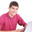 Smiling young man working on laptop isolated on white — Stock Photo
