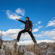 Young man with backpack on a mountain hike — Stock Photo