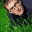 Young man in glasses is liyng in green grass — Stock Photo